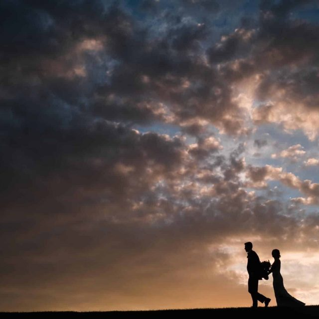 Couple walking in front of a beautiful sunset Lincoln Nebraska Wedding Photographer