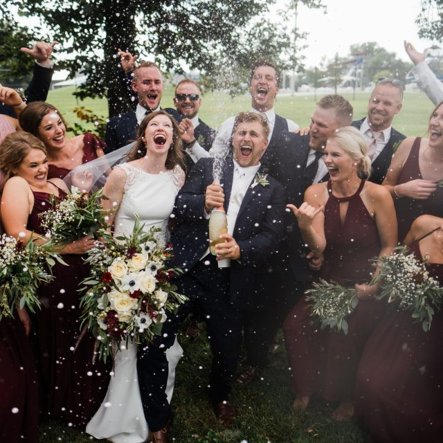 Newly married couple sprays a bottle of champagne with their wedding party after their Nebraska Wedding